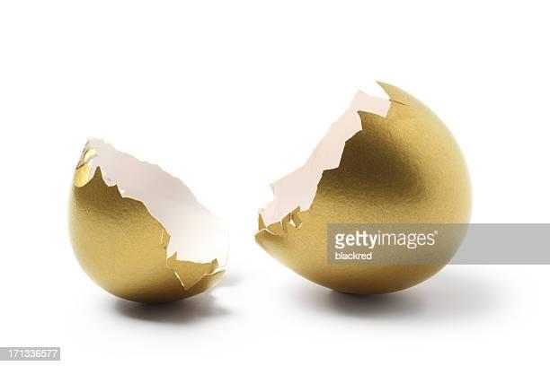 Coque fissurée ouvert Oeuf d'or sur fond blanc