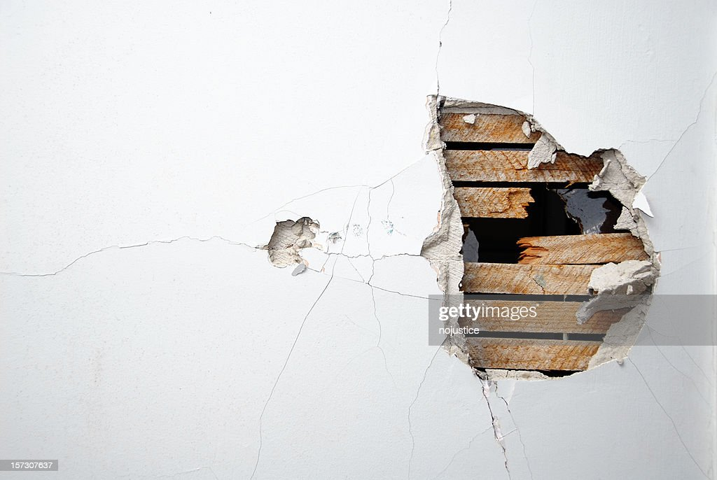Cracked plaster, drywall and wood of a home's white wall : Stock Photo