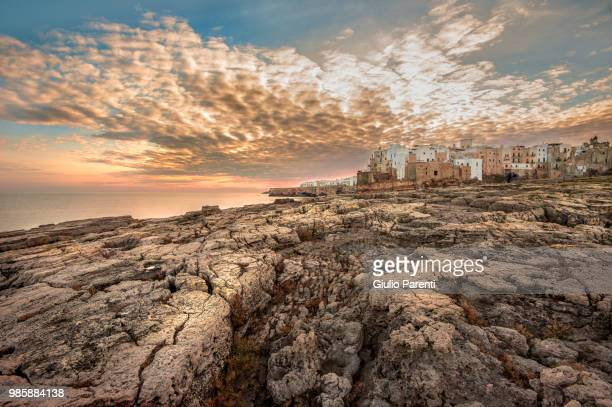 a cracked rocky coastline in polignano, italy. - ostuni stock photos and pictures