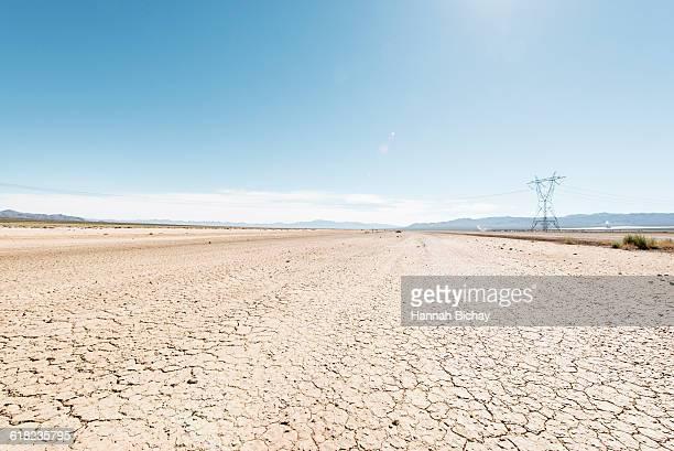 Cracked soil in Nevada desert with power line