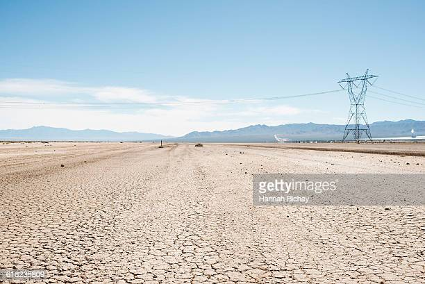 Cracked soil in Nevada desert with power line