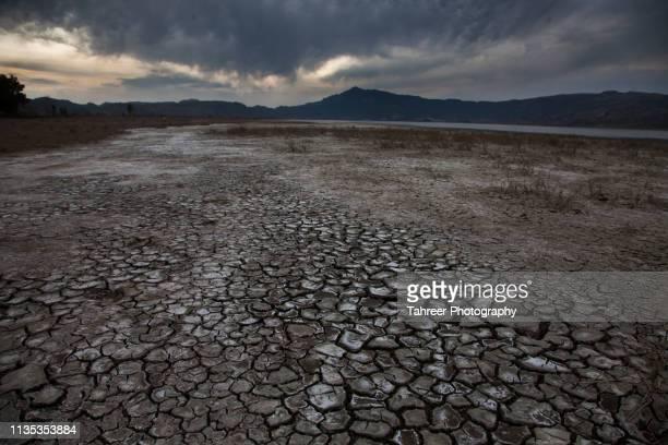 cracked soil with lake and mountain - erodiert stock-fotos und bilder