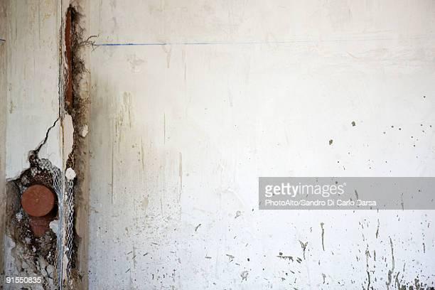 Cracked wall exposing plumbing fixture