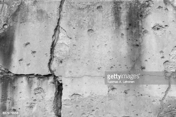 cracked wall with bullet holes - agujero de bala fotografías e imágenes de stock