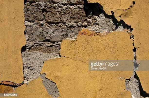 cracked yellow painted stucco on an adobe building exterior - adobe stock pictures, royalty-free photos & images