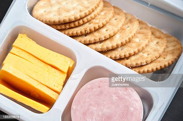 Crackers, sliced cheese and ham in a plastic tray