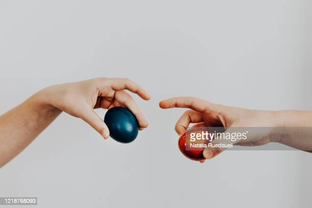 cracking hard-boiled eggs as traditional game on easter. playful imitation of michelangelo famous painting in the times of quarantine. -  キリスト教 伝来の地  ストックフォトと画像