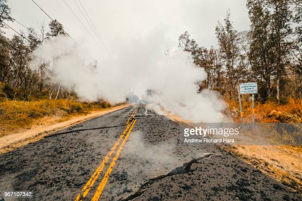 Cracks and volcanic debris are seen on a road on May 9 2018 in Leilani Estates Hawaii The first Hawaiian house was consumed this week by the...