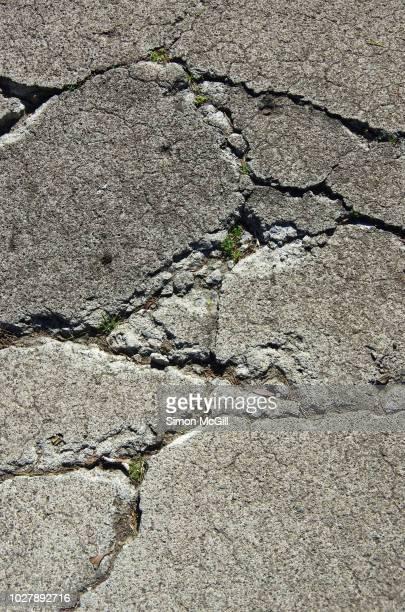 cracks in a concrete footpath - mala condición fotografías e imágenes de stock
