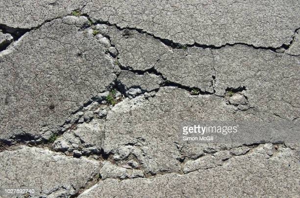 cracks in a concrete footpath - run down stock pictures, royalty-free photos & images