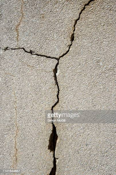 cracks in a concrete wall - cracked stock pictures, royalty-free photos & images