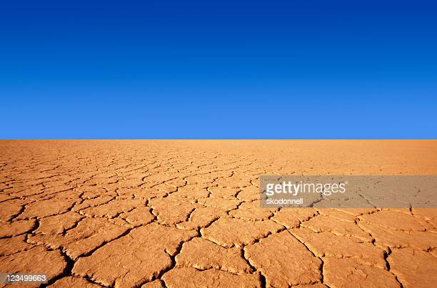 cracks in the desert and a blue sky - thirsty stock pictures, royalty-free photos & images