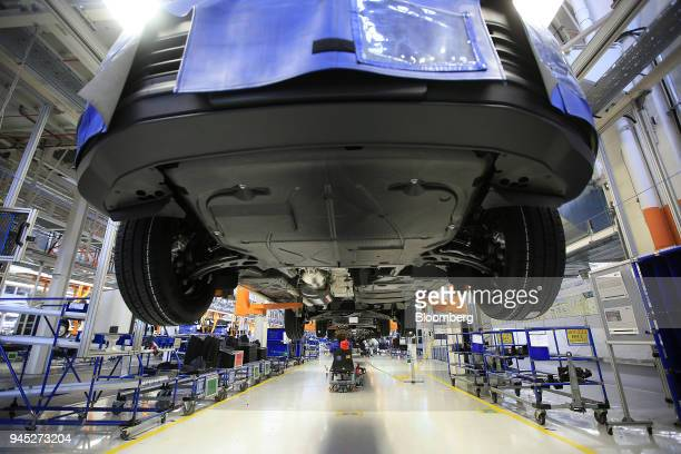 Cradled Volkswagen Transporter T6 panel vans are transported along underbody shield assembly line inside the Volkswagen AG factory in Hanover Germany...