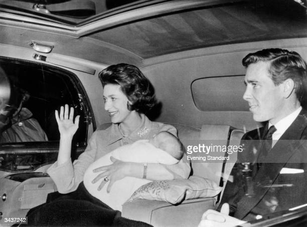 Cradling her new born son David Albert ArmstrongJones in her arms Princess Margaret Rose waves to the crowds In the car with her is her husband...