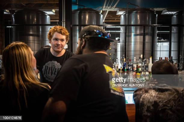 Craft beer brewer Jake Le Breton general manager at River Brew Co talk to clients in his brewery on June 29 2018 in the resort town of Victoria Falls...