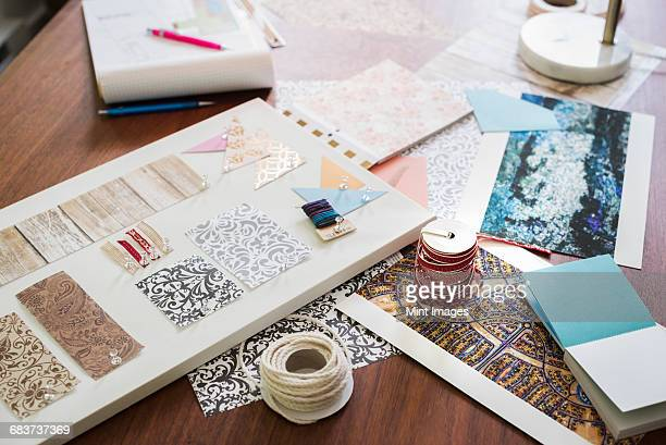 Craft materials, fabric and paper, patterns and a notebook and tablet.