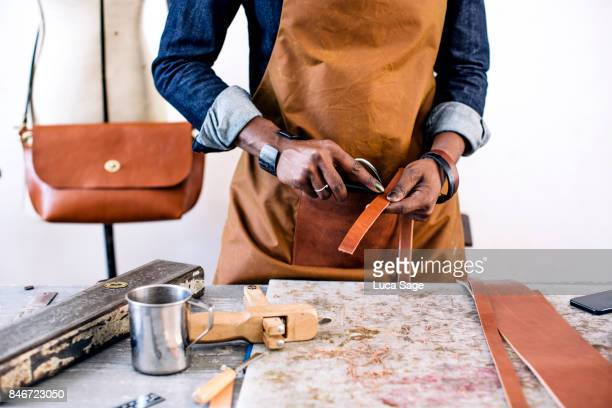 A craft person carefully making leather goods