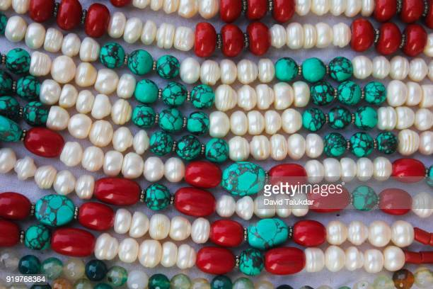 crafted jewellery of coral, turquoise and pearl - perlenschnur stock-fotos und bilder