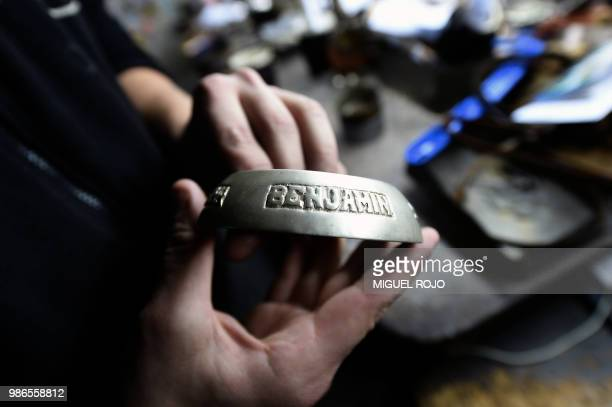 A craftman shows an engraved gold and silver ferrule for a mate at the workshop of traditional handmade silverware store Bresciani in Montevideo on...