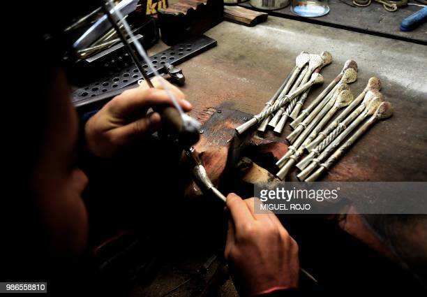 A craftman works on a gold and silver bombilla at the workshop of traditional handmade silverware store Bresciani in Montevideo on June 27 2018...