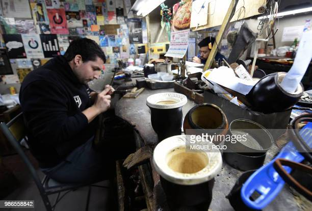 A craftman works on a gold and silver ferrule for a mate at the workshop of traditional handmade silverware store Bresciani in Montevideo on June 27...