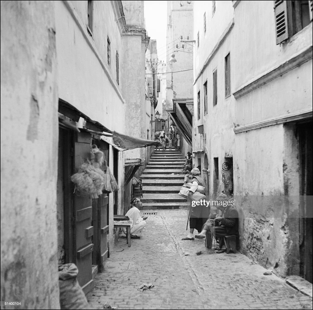 craftmen work and talk in a narrow street of the casbah in algiers