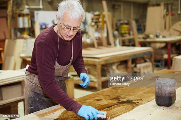 Craftsman applying wood stain to table