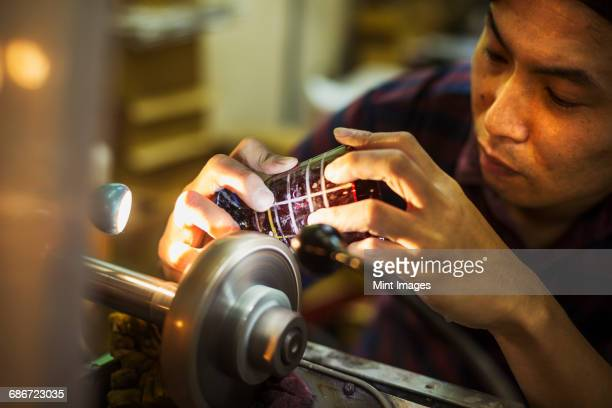 a craftsman at work at a machine, etching or scoring a coloured glass object.  - 美術工芸 ストックフォトと画像