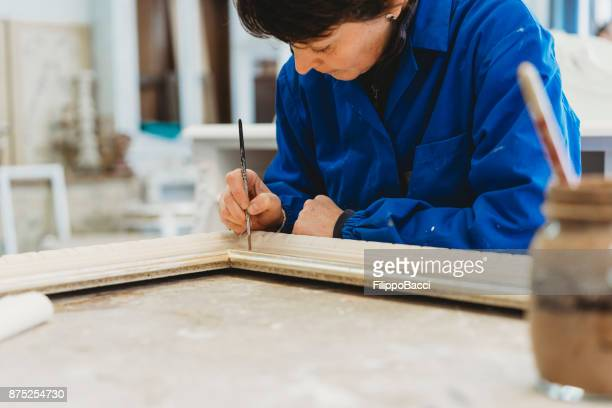 Craftsman carpenter painting a frame with brush