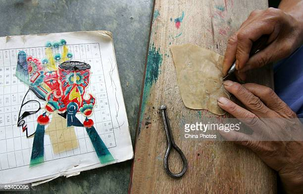 A craftsman carves a piece of leather to make puppet of a drama figure for Chinese Shadow Play August 17 2005 in Beijing China Chinese Shadow play...