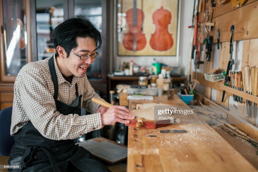 Artesano tallando un violín : Foto de stock