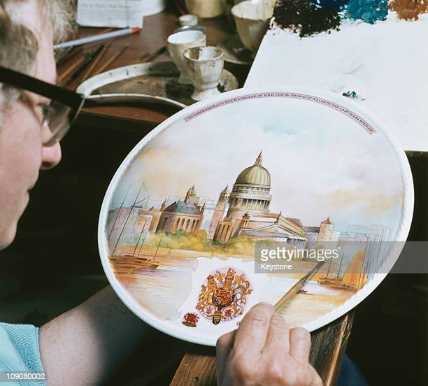 A craftsman completes an Aynsley wall plaque of St Paul's Cathedral to commemorate the wedding of Charles Prince of Wales and Lady Diana Spencer 1981