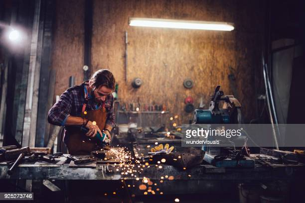 Craftsman cutting metal and using angle grinder in workshop