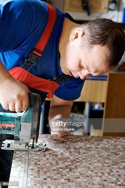 craftsman cutting wood with jigsaw