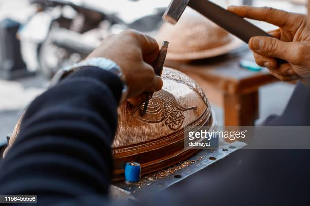 craftsman doing engravings on a copper metal plate - carving craft product stock pictures, royalty-free photos & images