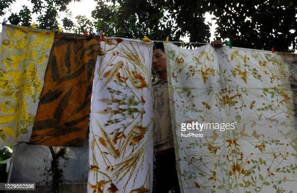 Craftsman dries a patterned cloth during fabric making using Eco-printing techniques at the Arae production gallery, in Bogor City, West Java,...