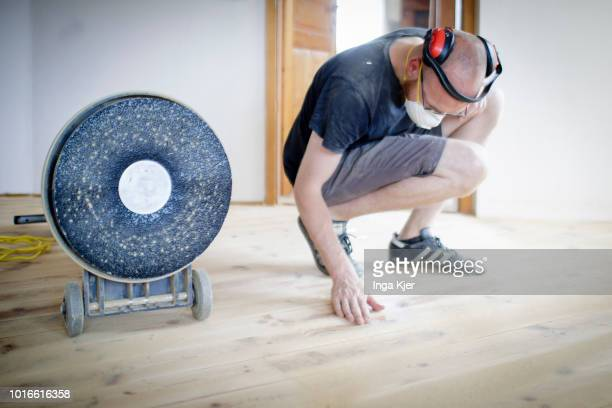 A craftsman feels about sanded wooden floorboards on July 24 2018 in BERLIN GERMANY Next to him is a grinder