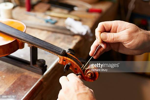 Craftsman fitting peg in violin repair workshop