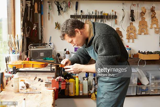 craftsman fitting peg in violin workshop - richard drury stock pictures, royalty-free photos & images