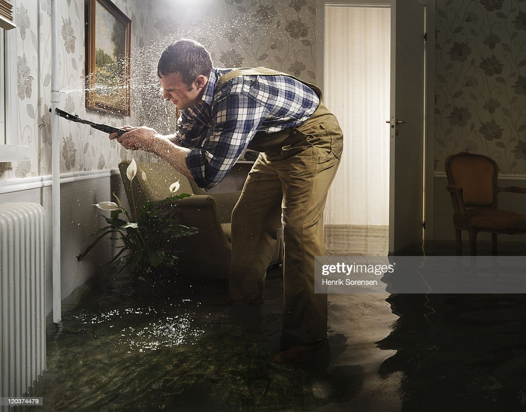 craftsman fixing pipe in flooded room : Stock Photo