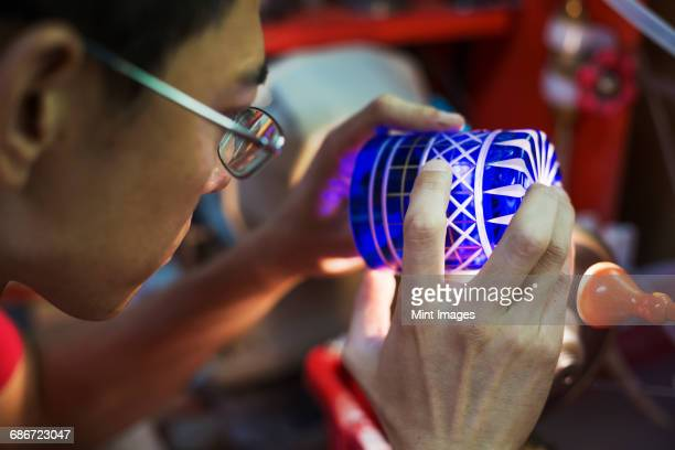 a craftsman glass maker holding a vivid blue cut glass cup, inspecting it closely.  - 工芸品 ストックフォトと画像