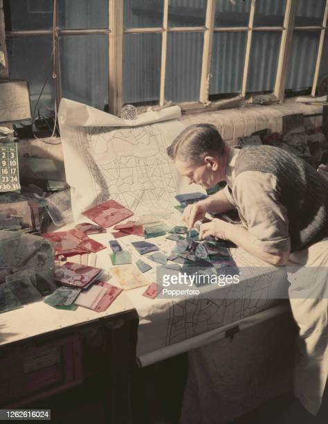 A craftsman glazier cuts coloured glass to fit the design for a stained glass window marked out on a paper plan below in a workshop at the...