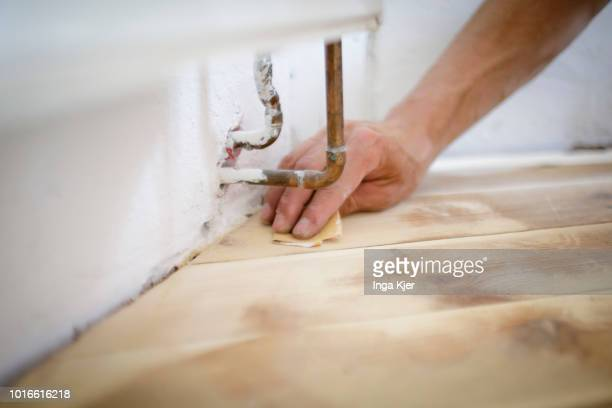 A craftsman grinds a floor made of wooden floorboards under a radiator by hand on July 24 2018 in BERLIN GERMANY