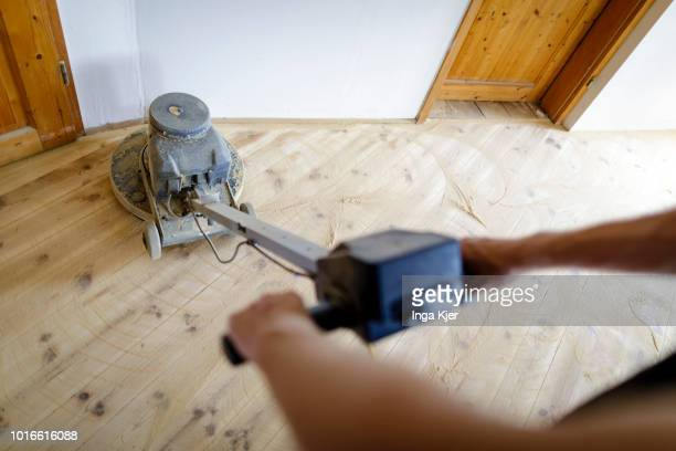 A craftsman grinds wooden planks with a grinder in an old building apartment on July 24 2018 in BERLIN GERMANY