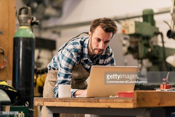 craftsman in metal workshop using laptop - maquinaria - fotografias e filmes do acervo