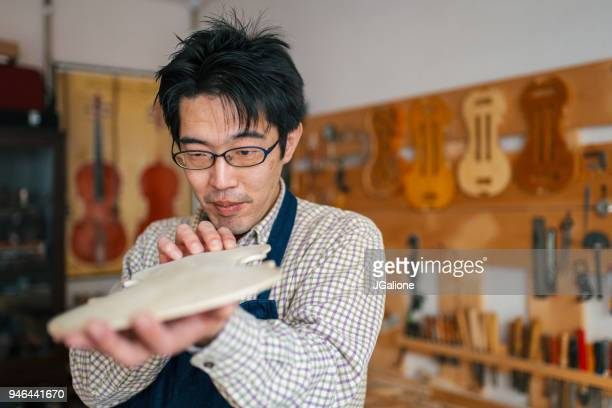 Craftsman inspecting the body of a recently carved violin