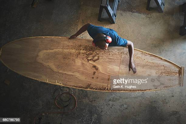 Craftsman making paddleboard in workshop, overhead view