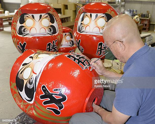 A craftsman of the Japanese traditional daruma doll paints the word hissho on the doll's body in Takasaki Gunma Prefecture in central Japan on June...