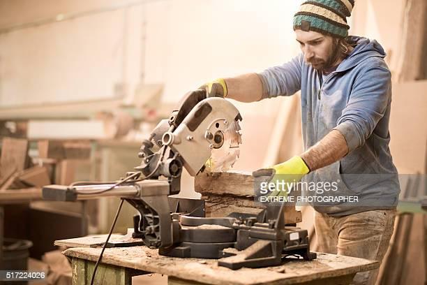 Craftsman operating on circular saw in workshop