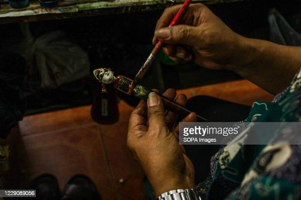 A craftsman painting a puppet of the Ramayana type in Bandung Cupumanik Gallery Cupumanik Puppets Gallery which was founded in 1970 has exported...